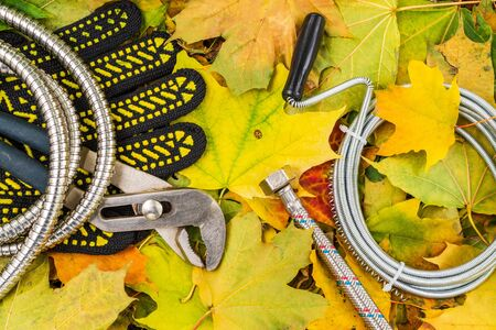 Necessary set tools for plumbers on on background of yellow leaves