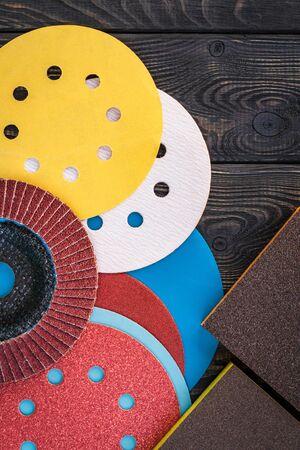 Set of abrasive tools and sandpaper different colors on black vintage wooden background
