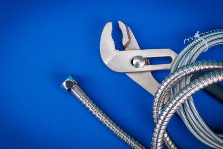 Plumbing tool and cable for connecting water hoses on blue background