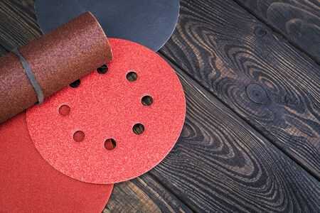 Set of abrasive tools and sandpaper different colors on black vintage wooden background 免版税图像