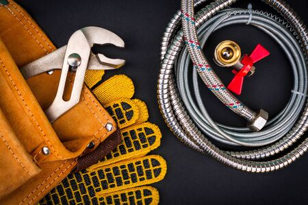 Plumbing tools in the bag for connecting water hoses on dark black background 스톡 콘텐츠