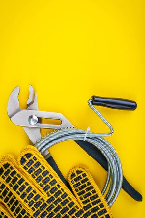 Plumbing tools, cable and gloves for connecting water hoses on yellow background