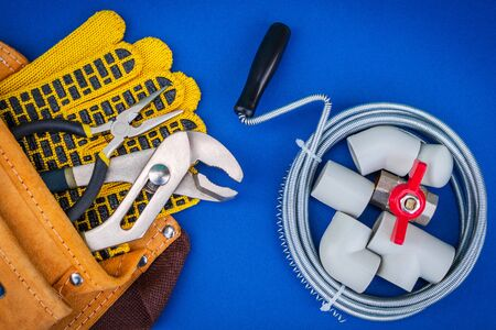 Plumbing tools, cable and gloves in bag for connecting water hoses on blue background