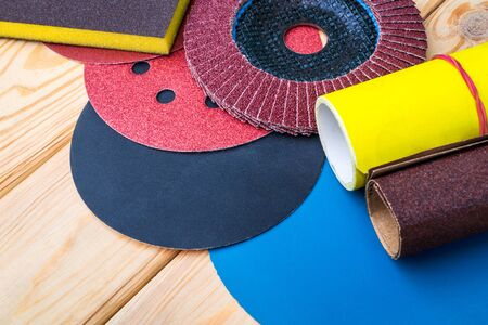 Set of abrasive tools different colors and sandpaper on wooden background. The wizard is used for grinding items
