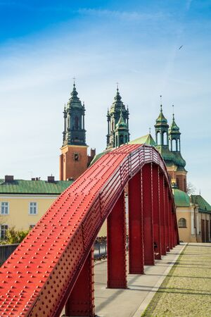 View of the red bridge and the Cathedral of Saints Peter and Paul in the Polish city of Poznan on the island of Tumsky Stock Photo
