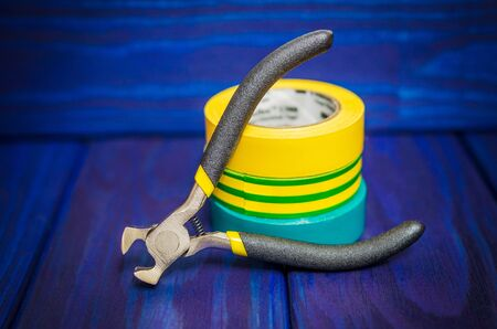 Three insulating tape and pliers for electrician on blue wooden boards closeup Standard-Bild - 133676189