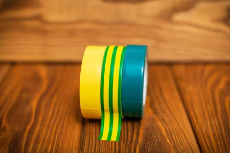 Three insulating tape for electrician on vintage wooden boards closeup Standard-Bild - 133676262