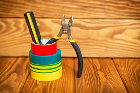 Insulating tape and tools for electrician on vintage wooden boards closeup Standard-Bild - 133676272