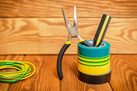 Three insulating tape for electrician on vintage wooden boards closeup Standard-Bild - 133676303
