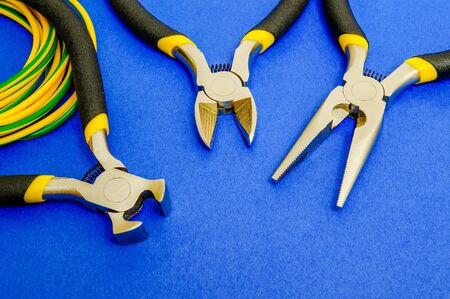 Pliers tool and wires for electrician closeup, service and repairing concept on blue background