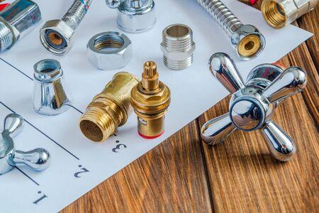 Pezzi di ricambio e accessori per la riparazione dell'impianto idraulico su un foglio di note Archivio Fotografico
