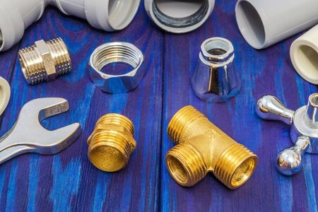 Spare parts with copper and plastic accessories for plumbing repair on wooden blue boards