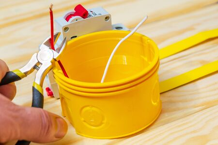 Electrician cuts red wir with pliers sticking out of a yellow box