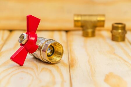 New ball water valve for plumbing with red handle on wooden boards