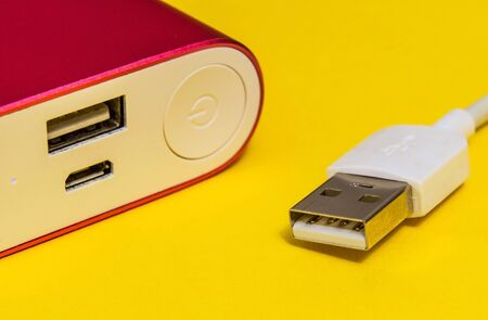Damaged USB charger cable and power bank on yellow surface close up used to charge a smartphone 免版税图像