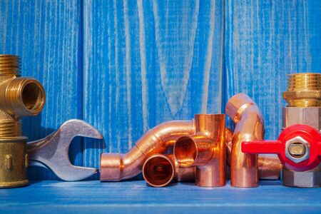 Spare parts with copper and plastic accessories for plumbing repair on blue vintage wooden boards Imagens