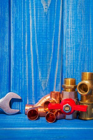 Spare parts with copper and plastic accessories for plumbing repair on blue vintage wooden boards
