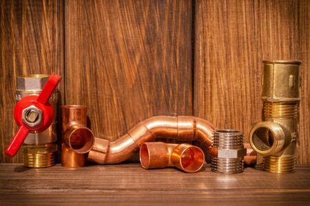 Spare parts with copper and plastic accessories for plumbing repair on vintage wooden boards