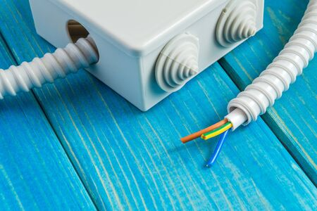 Junction box with wire for repairing electrics in house on blue wooden boards