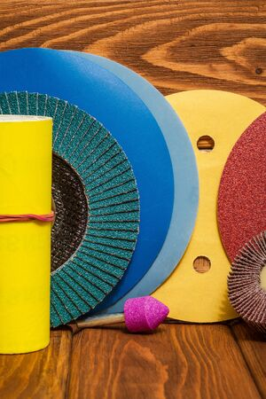 Big set of abrasive tools and multicolored sandpaper on wooden vintage background, wizard is used for grinding items 免版税图像
