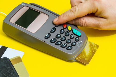 Hand entering pin code to money terminal before payment on yellow background