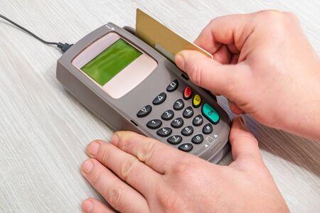 Die Hand führt eine Bankkarte in das Geldterminal ein, um in der Desktop-Draufsicht zu bezahlen Standard-Bild