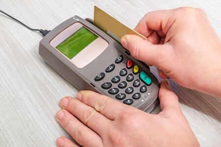 Hand inserts bank card into money terminal for payment on desk top view Banco de Imagens