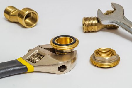 Set of brass fittings and tool is often used to connect for water and gas installations on gray background