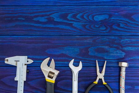 Necessary set of tools and hose for plumbers on wooden blue boards with space for advertising