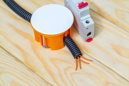 Electrical junction orange box with wires on wooden boards usually used in the electric installation process
