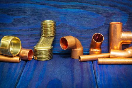 Copper water pipe fittings for soldering plumbing concept or repair water supply on blue wooden boards Standard-Bild