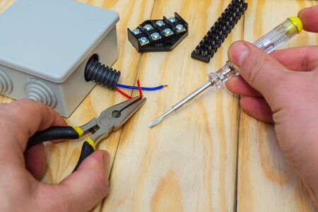 The master holds an electric tool and wires of different colors to connect