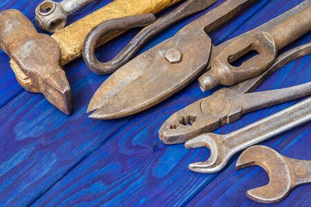 Many vintage craftsman tools stacked after work on blue wooden boards Archivio Fotografico
