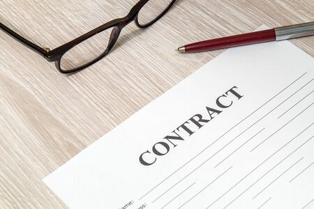 Contract form for filling with pen and glasses on table in the bank office