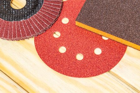 Big set of abrasive tools and yellow sandpaper on wooden boards, wizard is used for grinding items 免版税图像