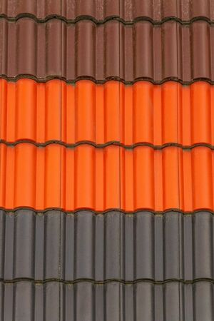 Metal tiles of different colors for the sample on the exhibition stand is used for roofing