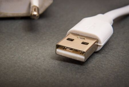 USB charger cable on dark surface close up often used for charging a smartphone or tablet Stock Photo