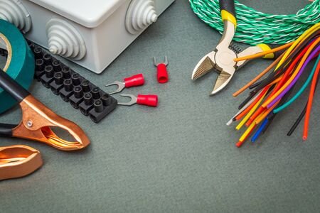 Spare parts, tool and many wires for replacement or repair of electrical equipment on a green-gray background