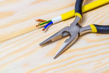 Pliers and wires for electrical prepared before repair or setting on wooden boards Stock Photo
