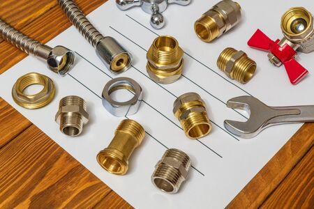 Many plumbing spare parts and adjustable spanner closeup on the sheet for notes and preparation of repair plan Stock Photo