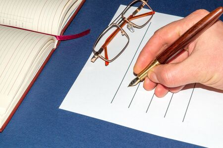 Businessman writes report on blue table in the office or bank, hand holds a pen