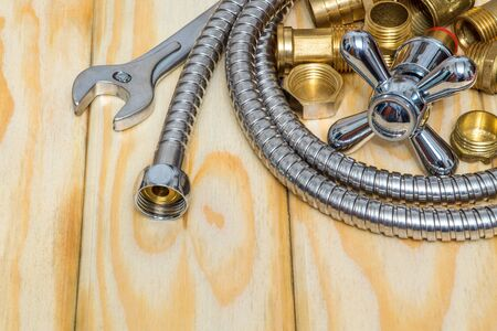 Plumbing materials, faucet, tools, fittings and hose on wooden boards used to replace or repair