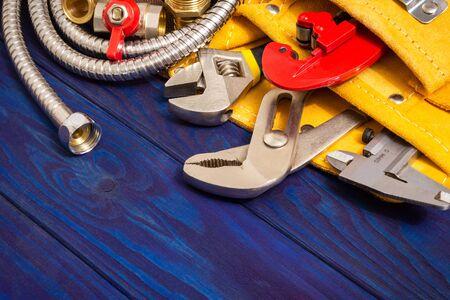 Plumbing tools in yellow bag and spare parts on blue wooden boards are used to replace or repair 版權商用圖片