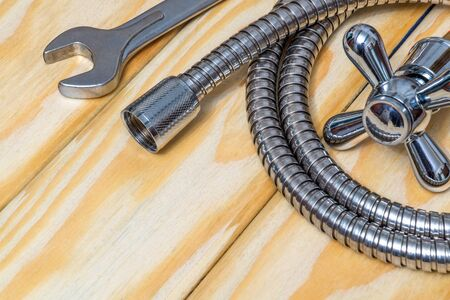 Plumbing materials, faucet and hose on wooden boards used to replace or repair