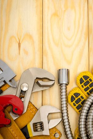 Plumbing tools in bag and hoses on wooden boards are used to replace or repair