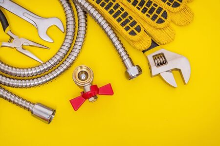 Plumbing tools and gloves for connecting water hoses on yellow table for work