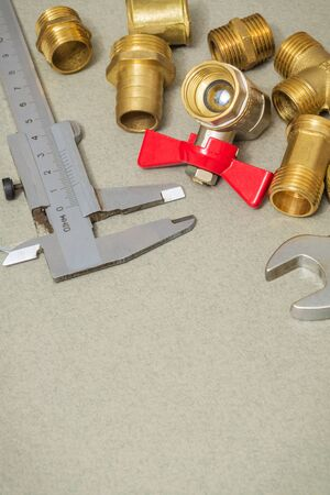 Plumbing materials faucet, tools and fittings on gray desk are used for replacement in shower