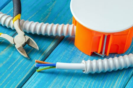 Junction box with wire and tools for repairing electrics in house on blue wooden boards Stockfoto