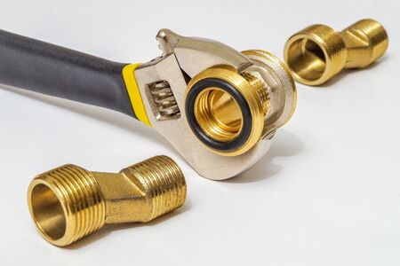 Set of brass fittings and tool is often used to connect for water and gas installations on gray background Stock Photo