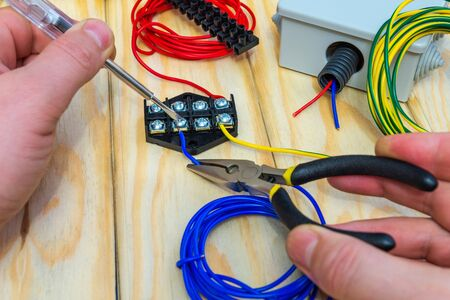 The master holds an electric tool and wires of different colors to connect Stock Photo